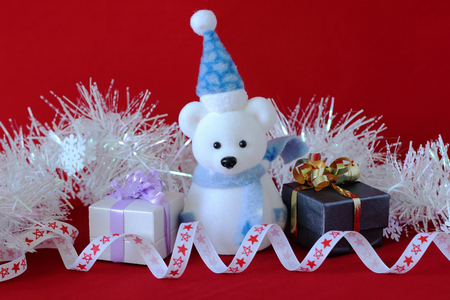 polar bear wearing a hat and a blue scarf posed next to a gift with shiny knots on a Christmas holiday decor Stock Photo