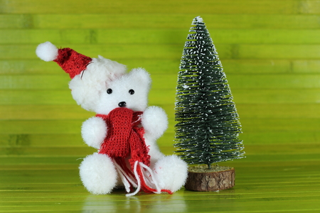 a toy polar bear with a hat and a scarf sitting next to a decorative tree with chrismas on a green wood background Stock Photo