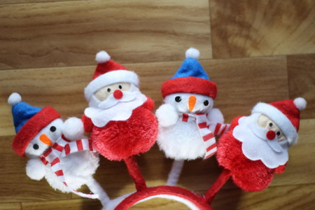 a stuffed santa claus and snowmen side by side