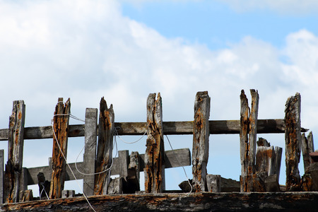 an old wooden fence against a background of a blue sky and white clouds Stock Photo