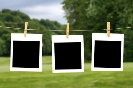 Three blank polaroid photos hanging on a string Stock Photo