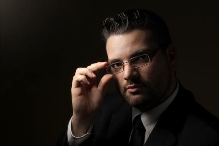 眼鏡のハンサムな男の低キーの肖像画