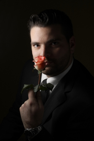 Low key portrait of handsome man with a rose Stock Photo - 8918419