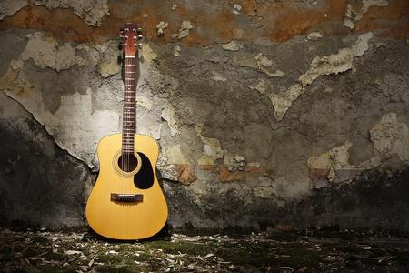 汚れた壁に寄りかかってアコースティック ギター 写真素材