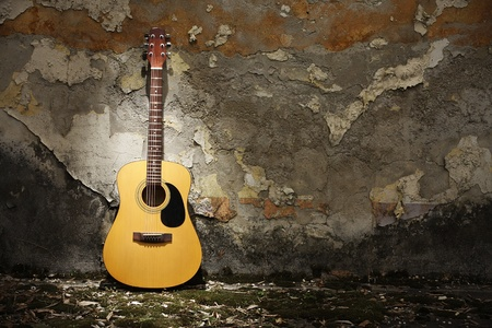 guitar: Acoustic guitar leaning on grungy wall