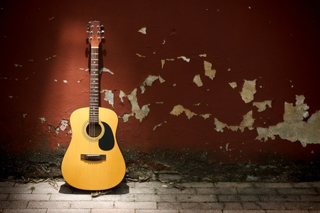 Acoustic guitar leaning on grungy wall photo