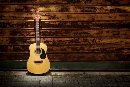 Acoustic guitar leaning  on rusty  gates