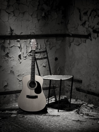 Guitar of a homeless man in grungy abandoned place Stock Photo