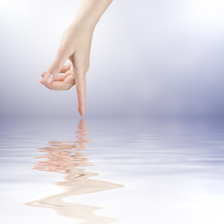 Female finger touching the water surface level Stock Photo - 8918477