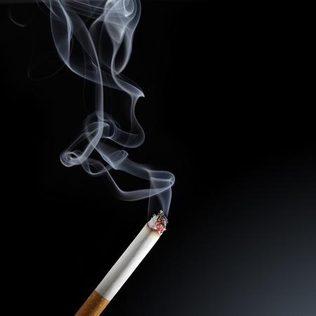 smoke: Brandende sigaret met rook op zwarte achtergrond
