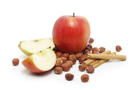 Apples, cinnamon sticks and hazelnuts on white Stock Photo - 8918322