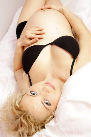 Beautiful young pregnant woman lying in bed photo