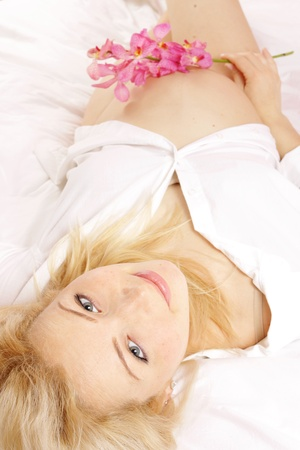 Beautiful pregnant woman in bed with pino orchid flower photo