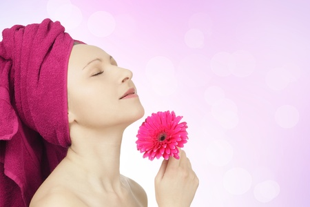 Young woman with towel and gerbera flower in spa Stock Photo - 8918812