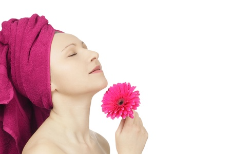 Young woman with towel and gerbera flower in spa photo