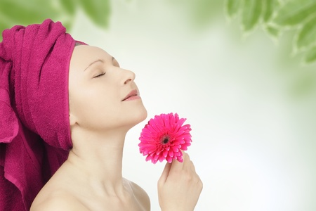 Young woman with towel and gerbera flower in spa
