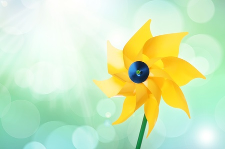 Yellow pinwheel toy against bokeh background photo