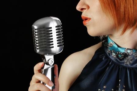 マイクを使ってレトロな赤毛の女性歌手