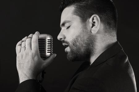 Portré férfi énekes régimódi mikrofon ellen fekete háttér Stock fotó