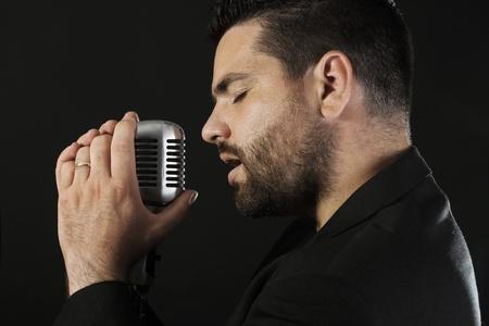黒い背景に対して古い昔ながらマイクを使って男性歌手のポートレート
