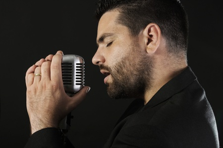 vocalist: Portrait of male  singer  with old fashioned microphone against black background