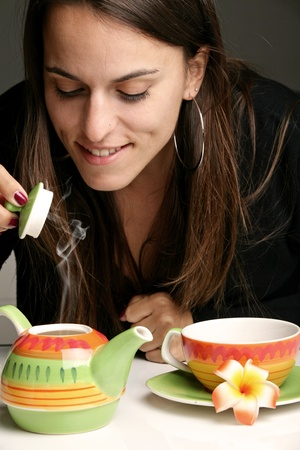 Woman pouring herself a cup of hot tea photo