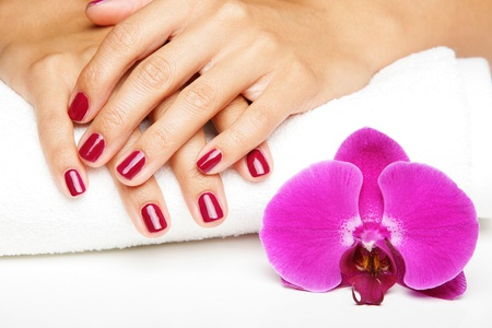 Beautiful hands with manicure and purple orchid flowers photo