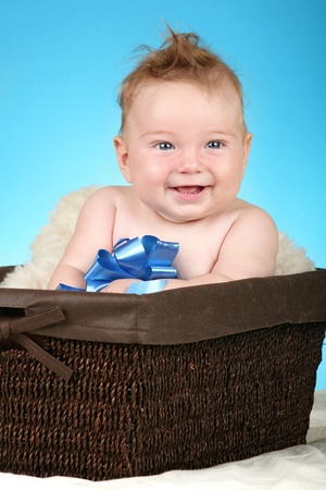 Adorable baby boy in wicker basket with blue bow photo