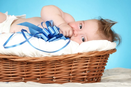 new born baby: Adorable baby boy in wicker basket with blue bow
