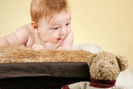 Adorable baby boy looking at his teddy bear photo