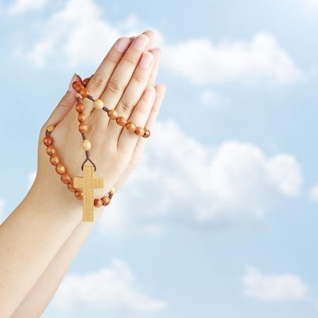 Hand egy rózsafüzért, kék ég