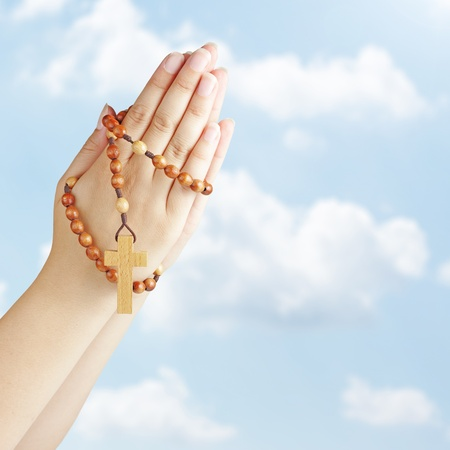 Hand with a rosary against blue sky 版權商用圖片 - 10448729