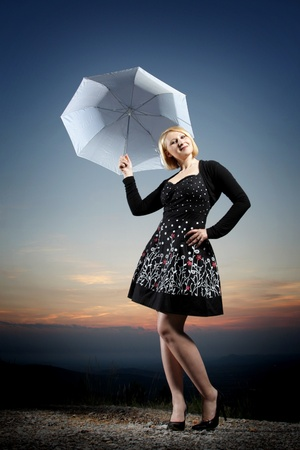 Young blonde woman with umbrella on the top of the hill Stock Photo - 10594282