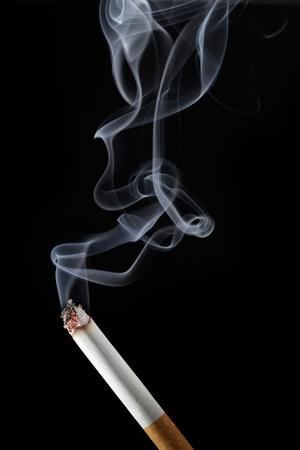 Burning cigarette with smoke on black background Stock Photo