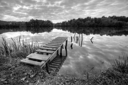 hdr: Beautiful lake with pier on cloudy day  in black and white