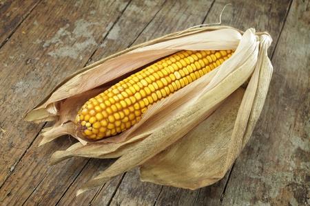 elote: Mazorca de maíz con las hojas en el escritorio de madera
