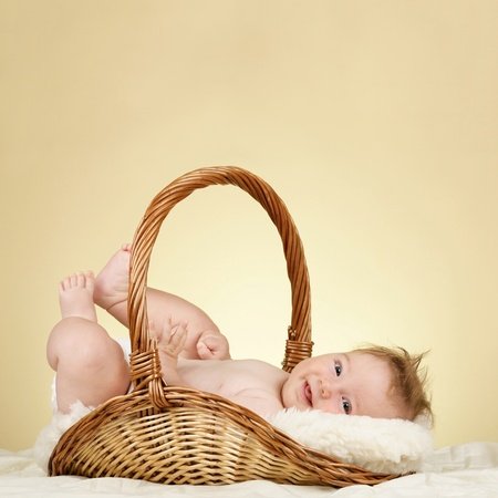Adorable baby boy in wicker basket photo