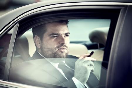 Wohlhabender Mann auf dem Rücksitz eines Autos Rauchen Standard-Bild