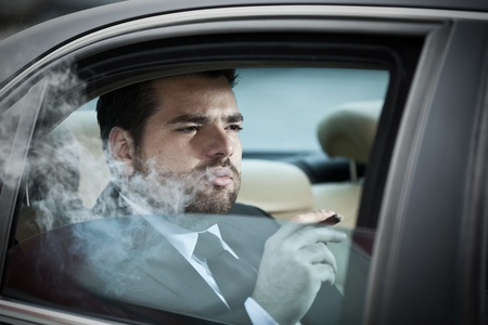 Wealthy man in the back seat of a car smoking photo