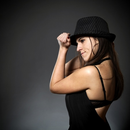 Beautiful young woman with hat dancing photo