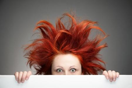 회색 배경에 지저분한 머리와 빨간 머리 여자