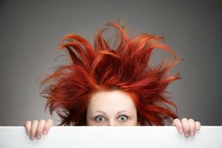 white hair: Redhead woman with messy hair against gray background Stock Photo