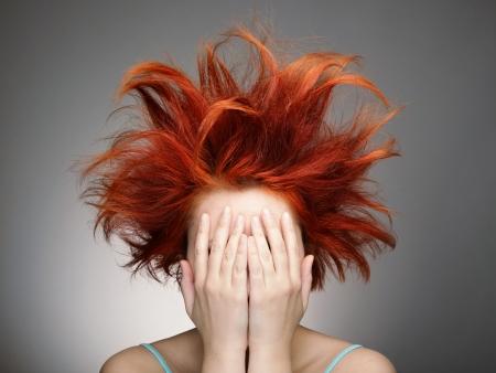pelo rojo: Pelirroja con el cabello desordenado cubri�ndose el rostro con las manos Foto de archivo
