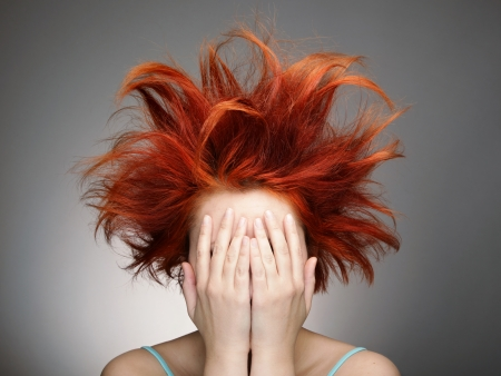 wild hair: Redhead with messy hair covering her face with hands