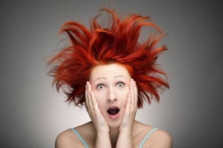 灰色の背景に対して厄介な髪と赤毛の女性