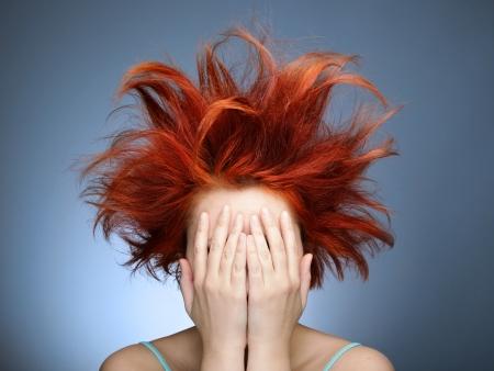 wild hair: Redhead con i capelli disordinati coprendosi il volto con le mani
