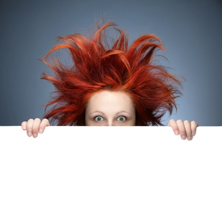 bad hair day: Redhead woman with messy hair against gray background Stock Photo