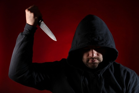 young knife: Dangerous man with knife against red background