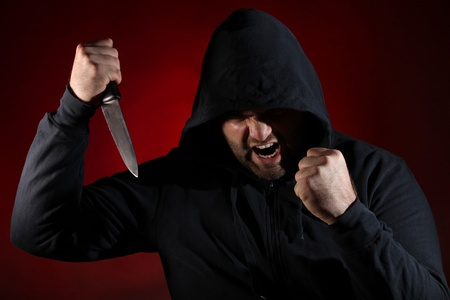 Dangerous man with knife against red background photo