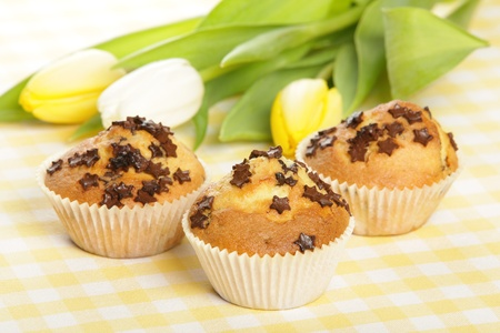 Home baked muffins with tulips in background photo